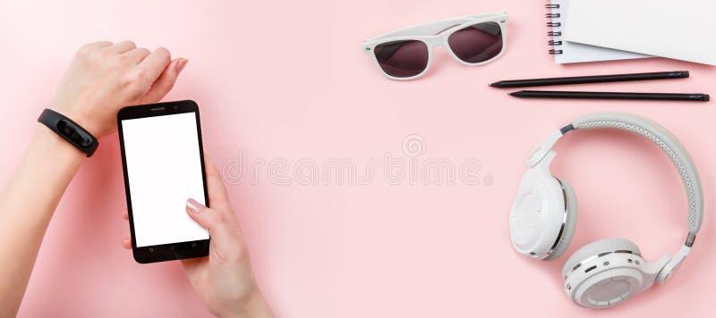 Baneråtlöje upp telefonen i händer med konditionbogseraren, hörlurar, exponeringsglas på rosa bakgrund fotografering för bildbyråer