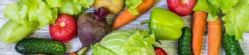 Baner av olika färgrika grönsaker över hela den oavkortade ramen för tabell ?ta som ?r sunt arkivfoton