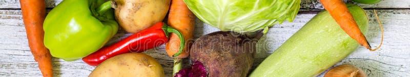 Baner av slutet upp av olika färgrika rå grönsaker på vit träbakgrund arkivfoton