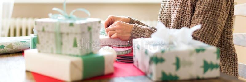 Baner för DIY-gåvainpackning Unrecognisable kvinna som slår in härliga nordiska stiljulgåvor täta händer upp royaltyfri bild