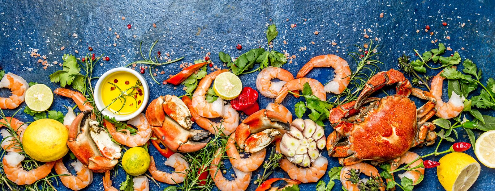 Baner. Fresh raw seafood - shrimps and crabs with herbs and spices on blue background. Copy space stock photo