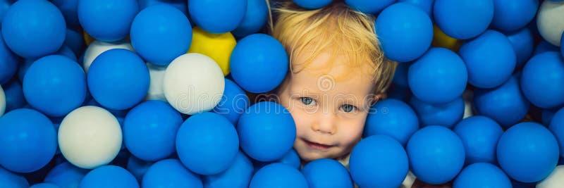 BANER LÅNGT FORMATbarn som spelar i bollgrop F?rgrika leksaker f?r ungar Dagis eller f?rskole- lekrum Litet barnunge arkivfoton