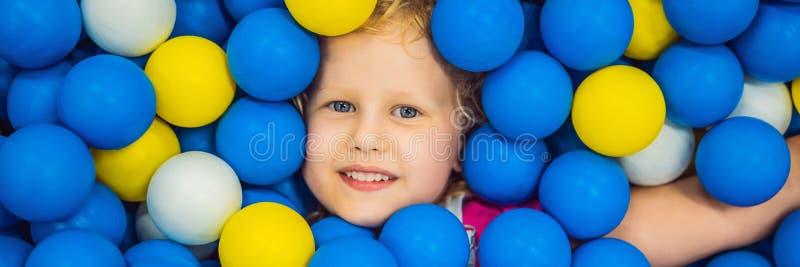 BANER LÅNGT FORMATbarn som spelar i bollgrop F?rgrika leksaker f?r ungar Dagis eller f?rskole- lekrum Litet barnunge royaltyfri bild