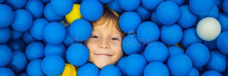 BANER LÅNGT FORMATbarn som spelar i bollgrop F?rgrika leksaker f?r ungar Dagis eller f?rskole- lekrum Litet barnunge arkivbilder