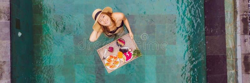 BANER LÅNGT FORMATfrukostmagasin i simbassängen som svävar frukosten i lyxigt hotell Flicka som kopplar av i p?len arkivfoton