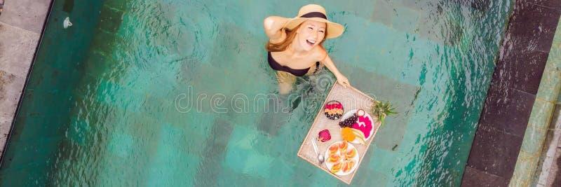 BANER LÅNGT FORMATfrukostmagasin i simbassängen som svävar frukosten i lyxigt hotell Flicka som kopplar av i p?len fotografering för bildbyråer