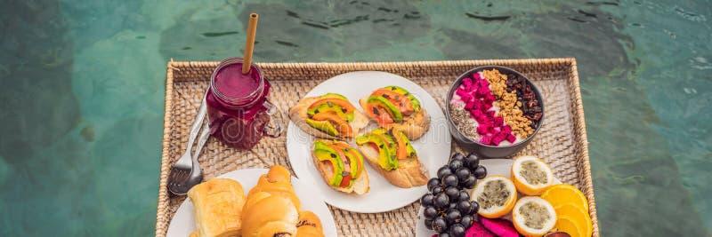 BANER LÅNGT FORMATfrukostmagasin i simbassängen som svävar frukosten i smoothies för lyxigt hotell och fruktplatta royaltyfri foto