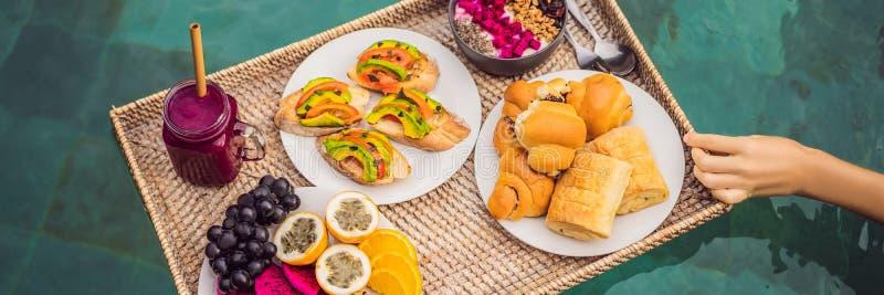 BANER LÅNGT FORMATfrukostmagasin i simbassängen som svävar frukosten i smoothies för lyxigt hotell och fruktplatta arkivfoto