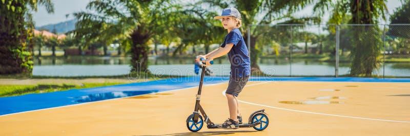 BANER lyckligt barn för LÅNGT FORMAT på sparksparkcykeln in på basketdomstolen Ungar l?r att ?ka skridskor rullbr?det pojke littl arkivbilder