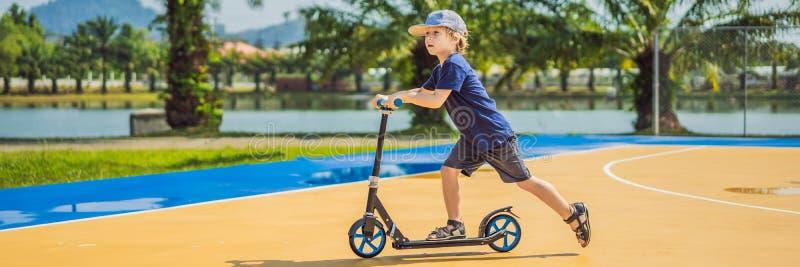 BANER lyckligt barn för LÅNGT FORMAT på sparksparkcykeln in på basketdomstolen Ungar l?r att ?ka skridskor rullbr?det pojke littl royaltyfria bilder