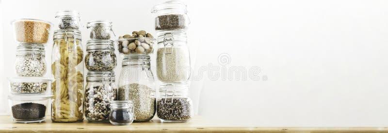 Baner med sortimentet av kornprodukter och pasta i exponeringsglaslagringsbehållare på trätabellen Sunt laga mat som är rent royaltyfria foton