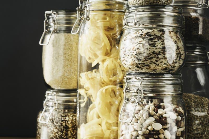 Baner med sortimentet av kornprodukter och pasta i exponeringsglaslagringsbeh?llare p? tr?tabellen Sunt laga mat som ?r rent arkivbild