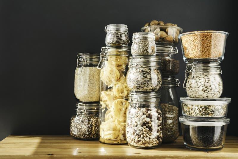 Baner med sortimentet av kornprodukter och pasta i exponeringsglaslagringsbeh?llare p? tr?tabellen Sunt laga mat som ?r rent fotografering för bildbyråer