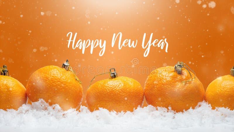 Baner med tangerin i form av julpynt på snön, med fallande snö Lycklig jul eller lyckligt nytt år, royaltyfri fotografi