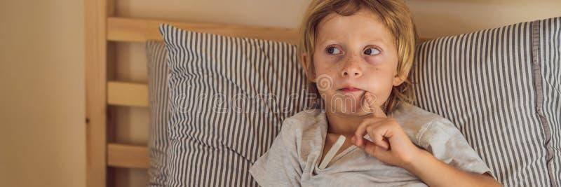 BANER sjuk pojke för LÅNGT FORMAT med termometern som lägger i säng- och faderhanden som tar temperatur kontrollera för fader arkivfoton