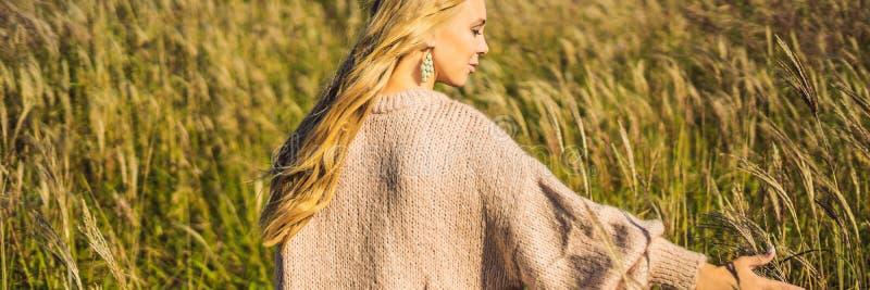 BANER ung härlig kvinna för LÅNGT FORMAT i höstlandskap med torra blommor, vetegrova spikar Modeh?st, vinter arkivfoto