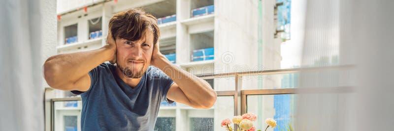 BANER ung man för LÅNGT FORMAT på balkongen som utanför förargas av byggnadsarbetena Ov?senbegrepp Luftförorening från fotografering för bildbyråer