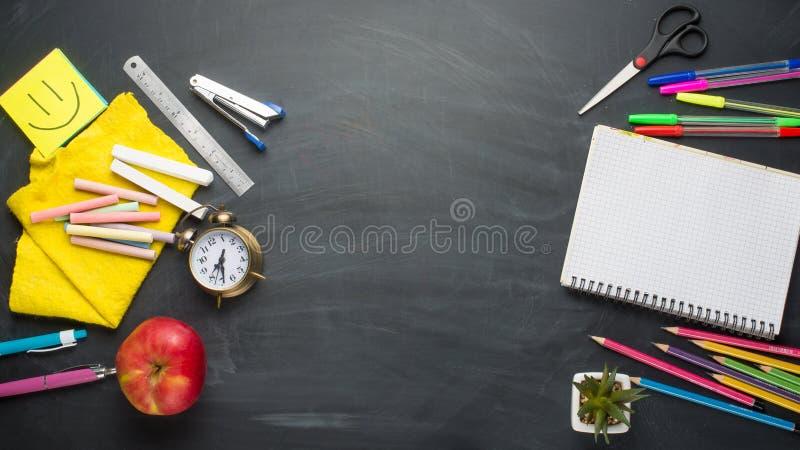 Banerbegreppsbaksida som skolar ringklockan, brevpapper för blyertspennaApple anteckningsbok på svart tavlabakgrund Accessorie fö royaltyfri fotografi