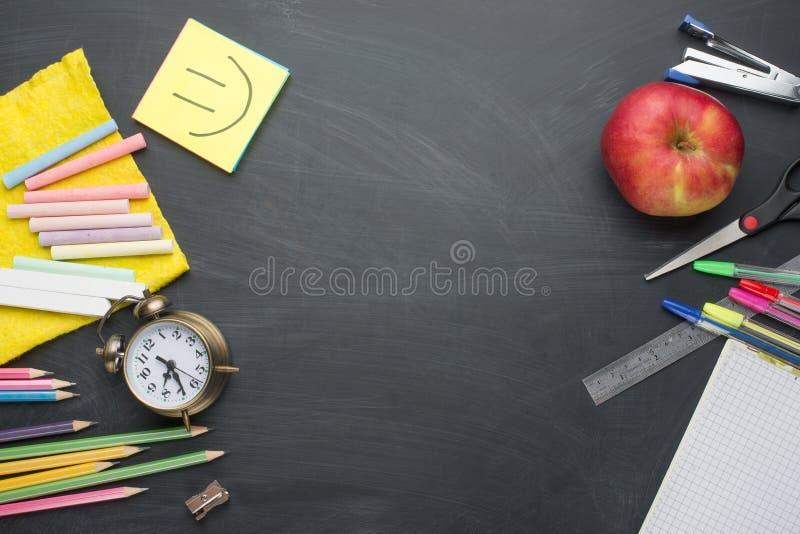 Banerbegreppsbaksida som skolar ringklockan, brevpapper för blyertspennaApple anteckningsbok på svart tavlabakgrund Accessorie fö royaltyfria foton