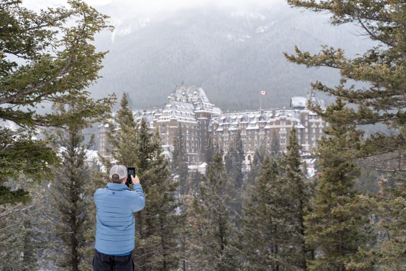 Banff, Alberta Canada - männliche touristische Fotografien eine Winterszenenansicht des berühmten Fairmont Banff Springs Hotel, s stockbild