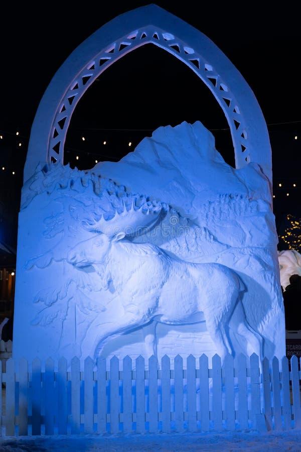 Banff, Alberta Canada - Schneeskulptur eines Elches und der Kanadier-Rocky Mountains-Berge belichtet nachts während Banffs stockfoto