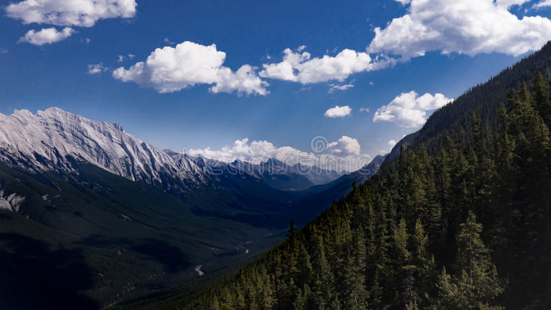 Banff Landscape. A lanscape shot of the Rocky Mountains from the Banff National Parke, high in the sky showing a blue sky with puffy white clouds, a vast stock photography