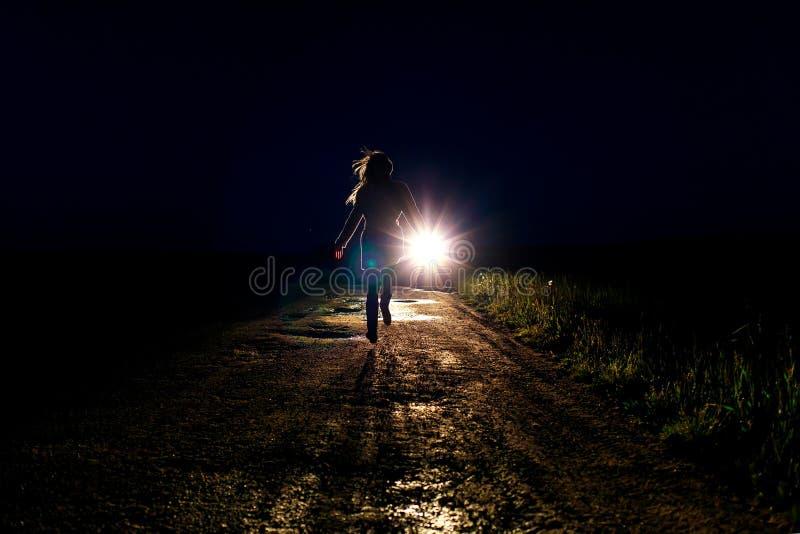 Bang gemaakt eenzaam lopend vrouwelijk silhouet op de nachtlandweg die vanaf achtervolgers op de auto in het licht van headli lop stock foto's