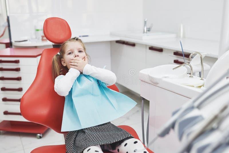 Bang gemaakt meisje bij tandartsbureau behandelde mond met handen stock foto
