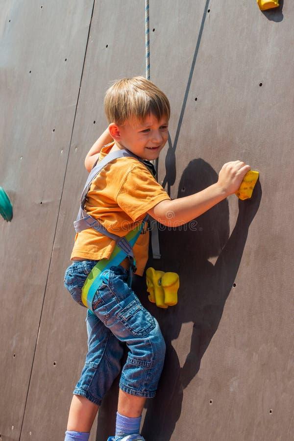 Bang gemaakt weinig jongen, omhoog op een kunstmatige rots met een veiligheidskabel wil beklimmen, is bezig geweest met bergbekli royalty-vrije stock afbeeldingen