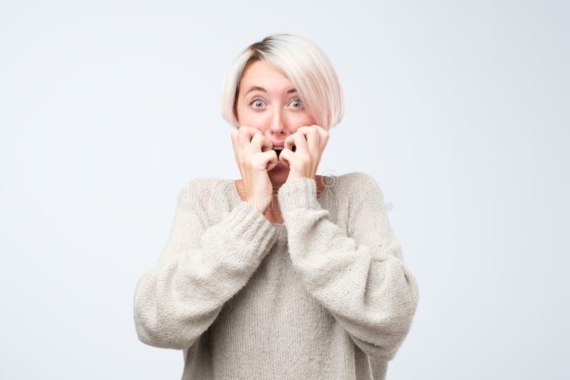 Bang gemaakte en beklemtoonde jonge vrouw die haar vingers bijten royalty-vrije stock afbeelding