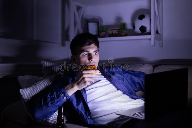 Bang gemaakte mens die pizza eten en op film op laptop letten stock foto