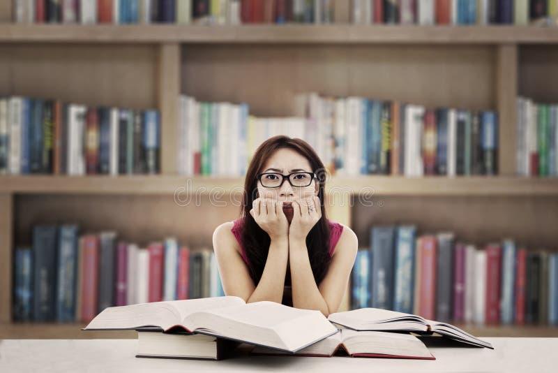 Bang gemaakte student in bibliotheek stock afbeeldingen