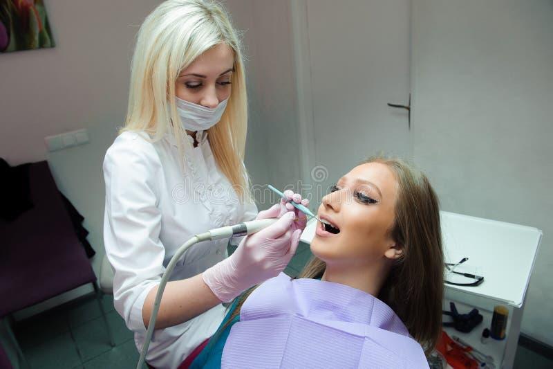 Bang gemaakte vrouwenzitting als voorzitter van de tandarts terwijl het bestuderen van de arts haar tanden stock afbeelding