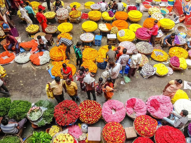 Flower sellers and their customers at colorful KR Market in Bangalore. Bangalore, India - Circa January, 2018. Flower sellers and their customers at colorful KR royalty free stock photos