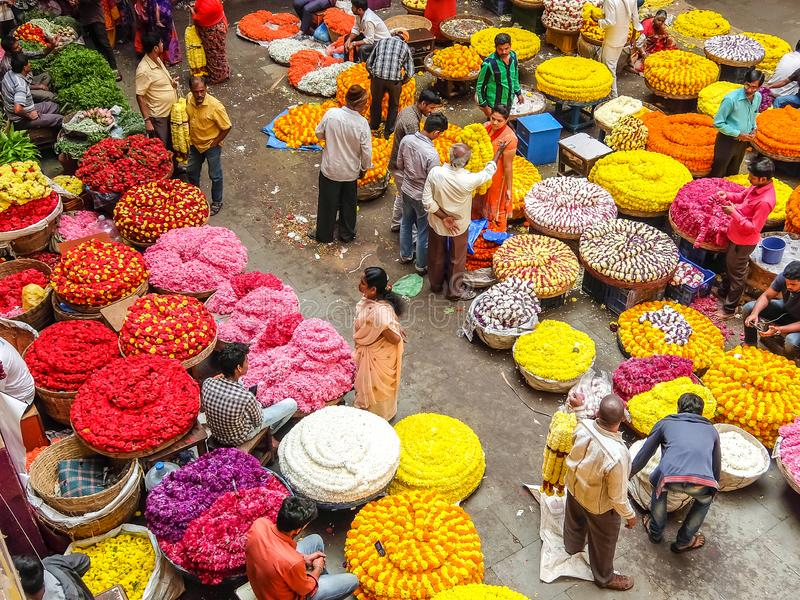 Flower sellers and their customers at colorful KR Market in Bangalore. Bangalore, India - Circa January, 2018. Flower sellers and their customers at colorful KR royalty free stock images