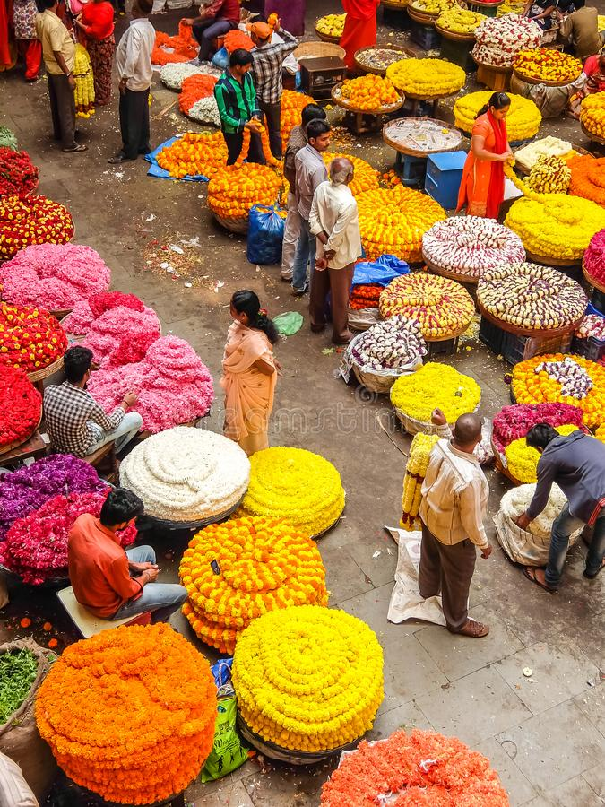 Flower sellers and their customers at colorful KR Market in Bangalore. Bangalore, India - Circa January, 2018. Flower sellers and their customers at colorful KR stock photos