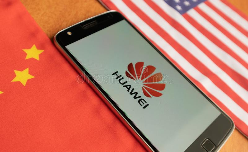 Bangalore, India, il 4 giugno 2019: Logo di Huawei in cellulare, tenuto fra la bandiera della porcellana e degli Stati Uniti fotografia stock