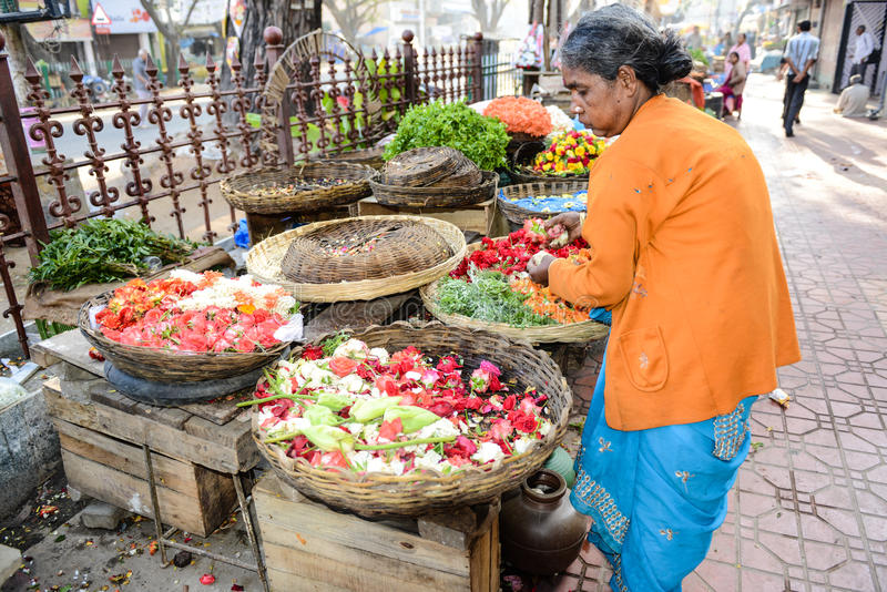 Bangalore India. BANGALORE, IN - JANUARY 09: Vendor sells flowers on the street in Bangalore, IN January 09, 2013 in Bangalore, India. 42% of India falls below royalty free stock photo