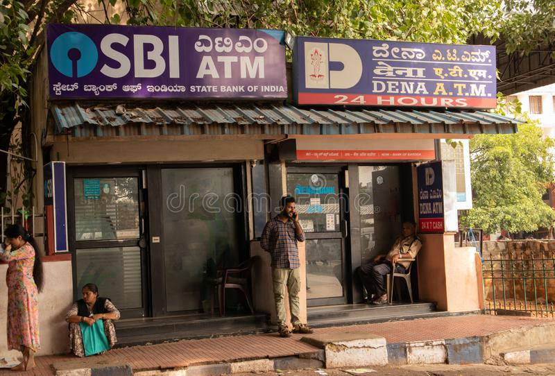 BANGALORE INDIA June 3, 2019 :People sitting infront of the SBI ATM and DENA bank ATM`s at bangalore railway station. BANGALORE INDIA June 3, 2019 :People royalty free stock images