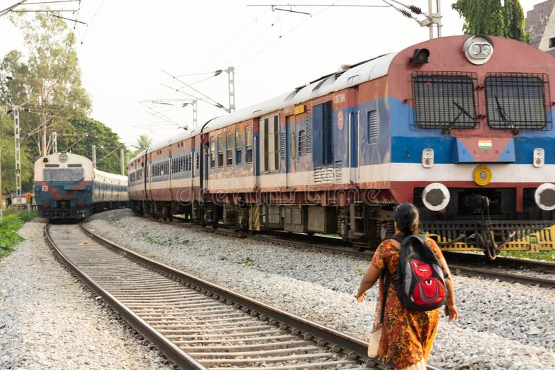 BANGALORE INDIA June 1, 2019 : Woman urban worker with backpack is walking on railway track line infront of the train in India stock photos