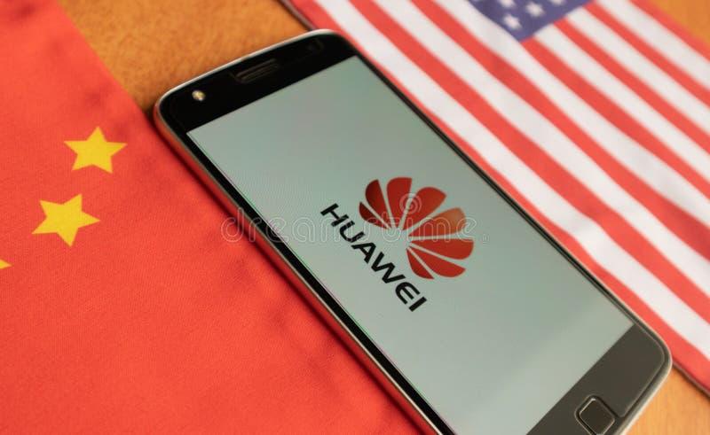 Bangalore, India, 4 Juni, 2019: Huaweiembleem in Mobiel, binnen gehouden - tussen de vlag van de V.S. en van China stock fotografie