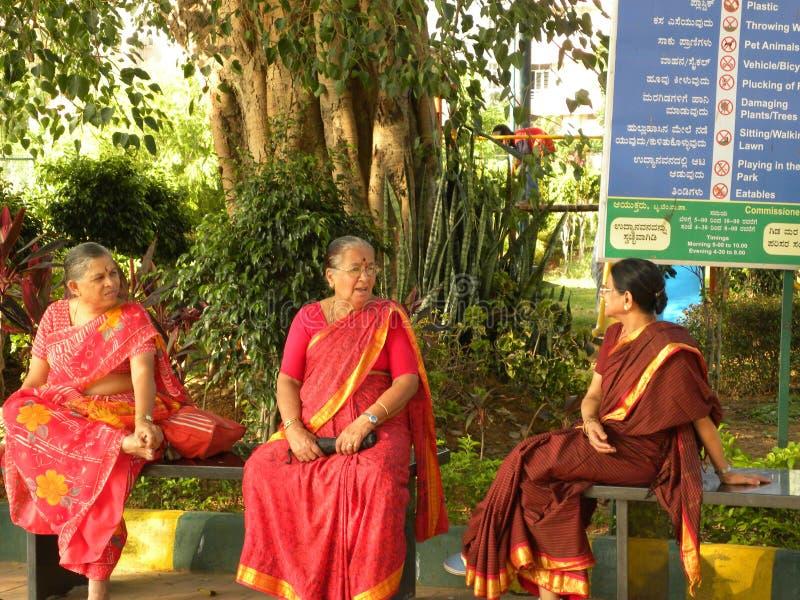 Bangalore, Karnataka, Inde - 2 juin 2010 3 femmes agées s'asseyant sur le banc et causant au jardin images stock