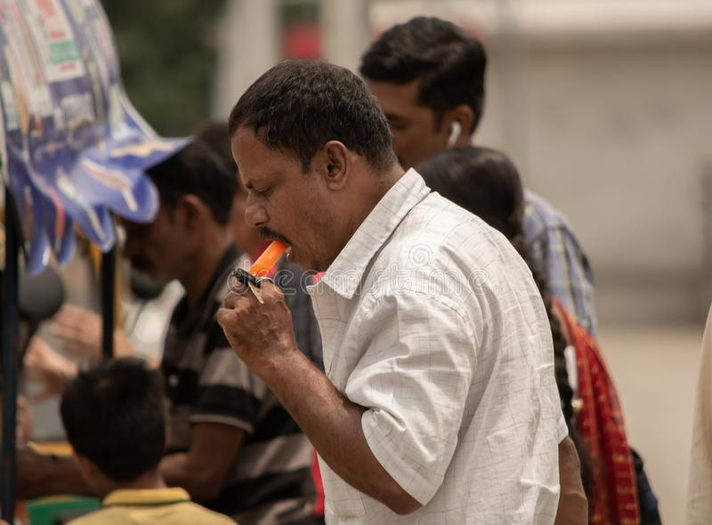 Bangalore, Karnataka India-June 04 2019 : Man eating ice cream on hot sunny day near Vidhana Soudha at bengaluru.  royalty free stock photography