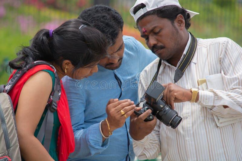 Bangalore, Karnataka Indien 4. Juni 2019: Der indische Fotograf, der den Kunden auf Fotokameraschirm Fotos zeigt, verbinden das B lizenzfreies stockbild