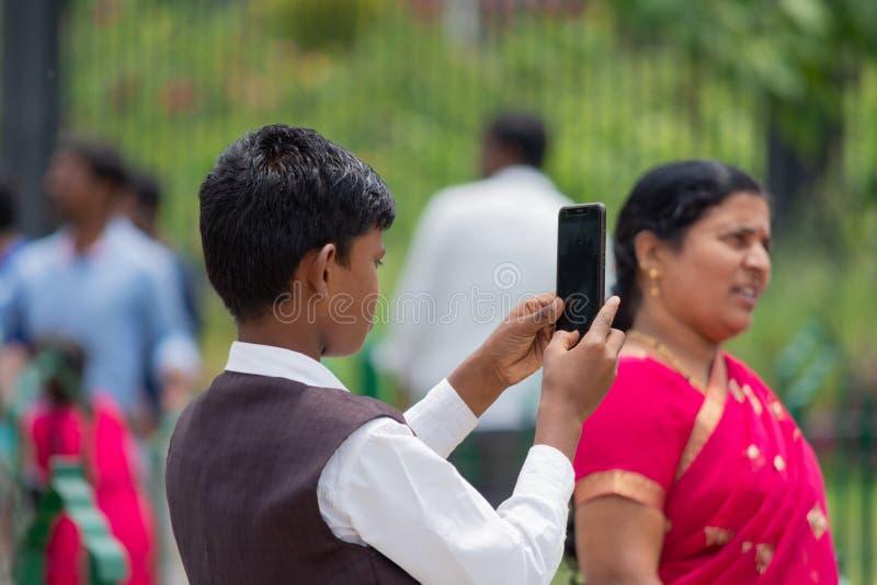 Bangalore, Karnataka Indien 4. Juni 2019: Indischer Junge, der zum Machen eines Fotos mit seinem Smartphone am vidhana Soudha Ben stockfotografie