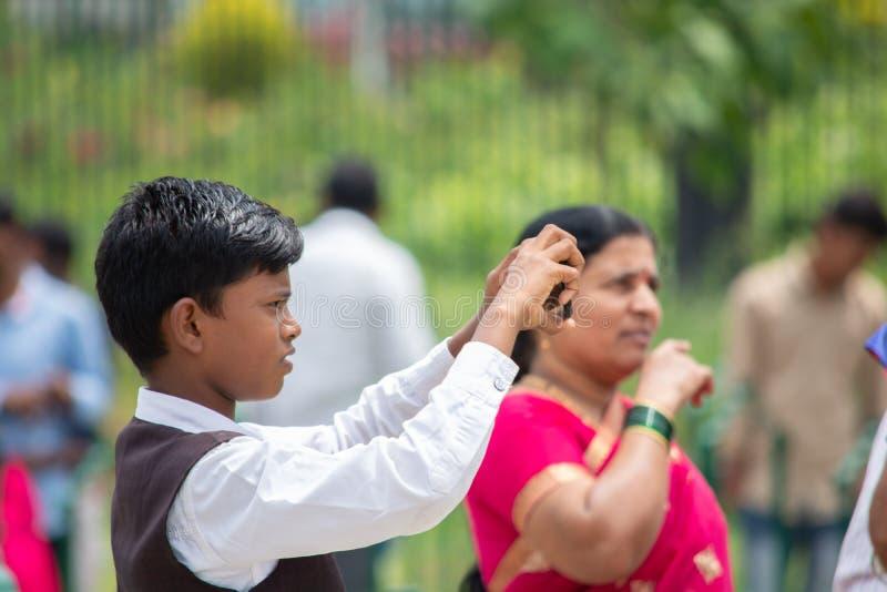 Bangalore, Karnataka la India 4 de junio de 2019: Muchacho indio que intenta a tomar una foto con su smartphone en el vidhana Sou imagen de archivo