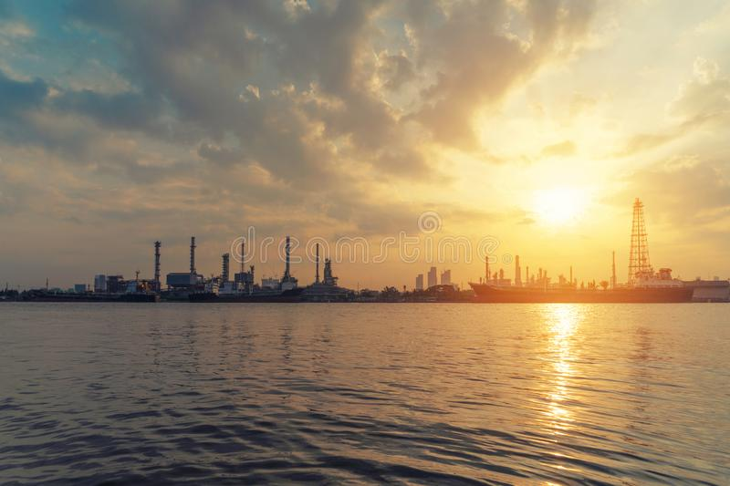 Bangchak Petroleum`s oil refinery with the sun at sunrise in ind. Ustrial engineering concept. Water reflection. Oil and gas industry. Urban city, Bangkok royalty free stock images