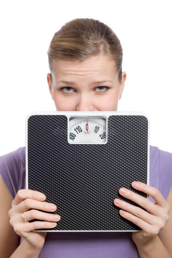 Bange jonge vrouw die achter een gewichtsschaal kijkt stock afbeelding