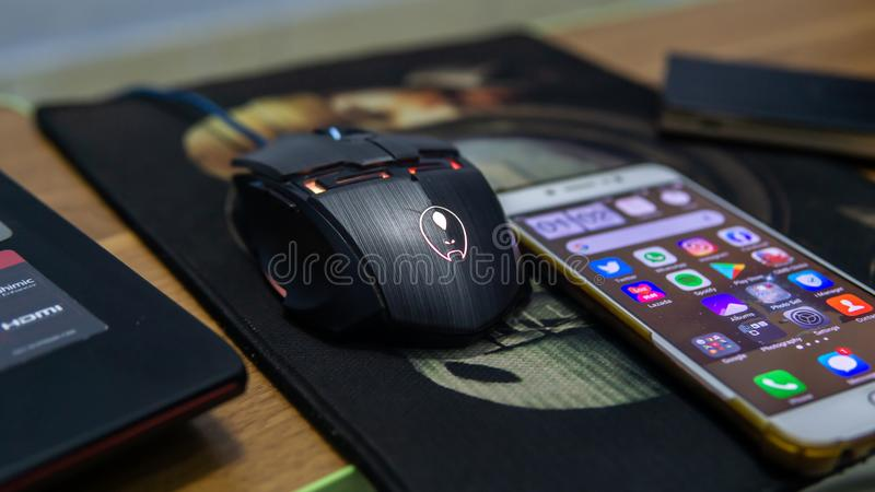 Close up view of a RGB led gaming mouse and an android smartphone on a mousepad royalty free stock photos