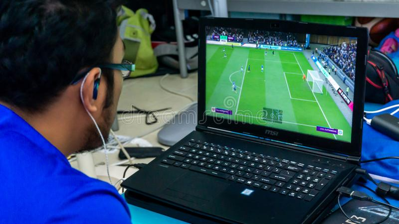 A man playing Fifa 19 on gaming laptop using a console stock photos